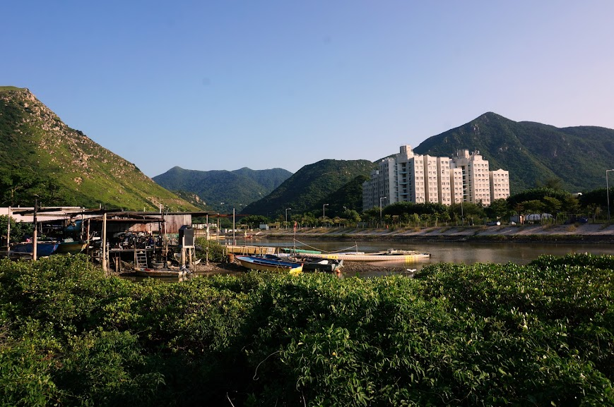 Contrast of a fishing village to modern apartment buildings