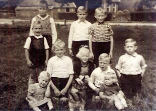 Photo: Bij de koel aan de Kerkstraat Van boven naar beneden en van links naar rechts: Henk Sloots, Jop Boelens, Willem Nijhof. 2e rij: Marchienus Sloots, Jans Oosting, Jantiena Nijhof, Jan Oosting en Jannes Boelens. Vooraan: Aly Nijhof Kl.d., de hond en Grietje Oosting. Foto gemaakt door Berend Oosting ± 1948