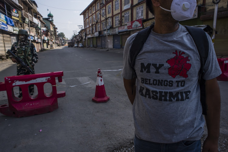An Indian paramilitary trooper stands guard on a deserted road in the city center's commercial hub, as a kashmiri man walks in front of him during a curfew in Srinagar, the summer capital of Indian administered Kashmir, India. Picture: Yawar Nazir/Getty Images