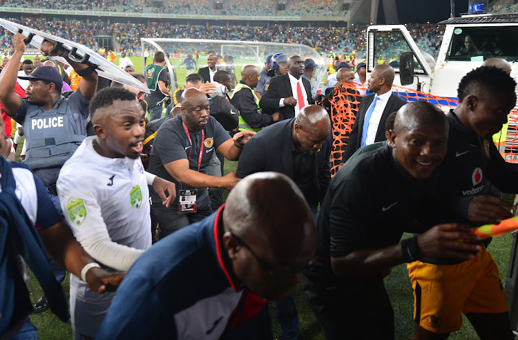 Kaizer Chiefs head coach Steve Komphela runs for cover along with Free State Stars' players and match officials after a Nedbank Cup semifinal, which Stars won 2-0, turned violent as Chiefs fans invaded the pitch baying for Komphela's blood shortly after the final whistle at Moses Mabhida Stadium in Durban.
