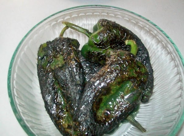 Char the skins of the peppers on the stove or grille. When they are...