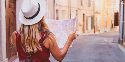 A woman is walking around the street with a map in her hand