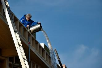 Photo: 20-11-2012 © ervanofoto Met een speciale stofzuiger wordt het dak droog gemaakt zodat de isolatie gelegd kan worden. En natuurlijk moet de ton af en toe eens geleegd worden.