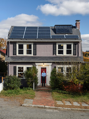 A person stands, smiling, on the doorstep of an older house retrofitted with solar panels