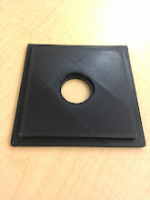Photo: First attempt at making a camera part - lens board for an old 4x5.  Model made in Openscad. Pretty proof of concept, but unusable - The bed heaters came online _after_ the part started printing, so there is some corner lifting, the smaller bore was .2mm too small (error in model), and an offset introduced by the minkowski function for corner radiusing has the hole not centered.
