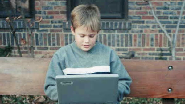 A blonde child sitting on a bench working on a laptop