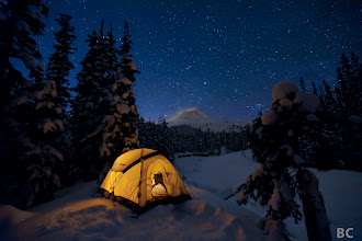 Photo: Glowing tent in snowy forest, Mt Hood in distance blows plume of snow, Winter stars shine above everything. A frozen stream bed flows below the ridge