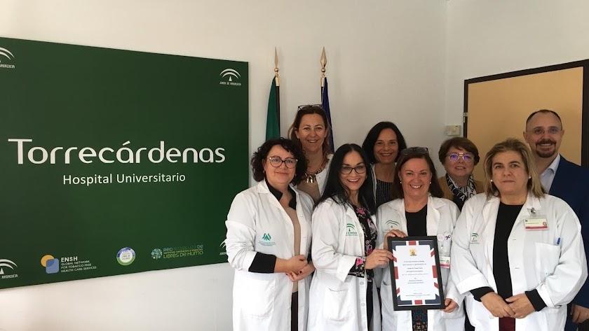 La Unidad de Trabajo Social de Torrecárdenas junto a un representante de la embajada británica con la placa de agradecimiento.