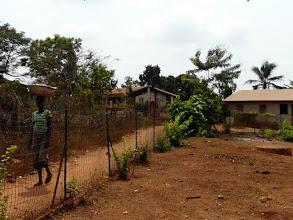 Photo: installée depuis plus de 10 ans par le CTM, la clôture grillagée résistante  protège l'enclos du dispensaire. On aperçoit le puits au fond