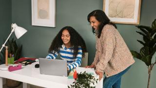 una adolescente y una mujer mirando juntas un ordenador