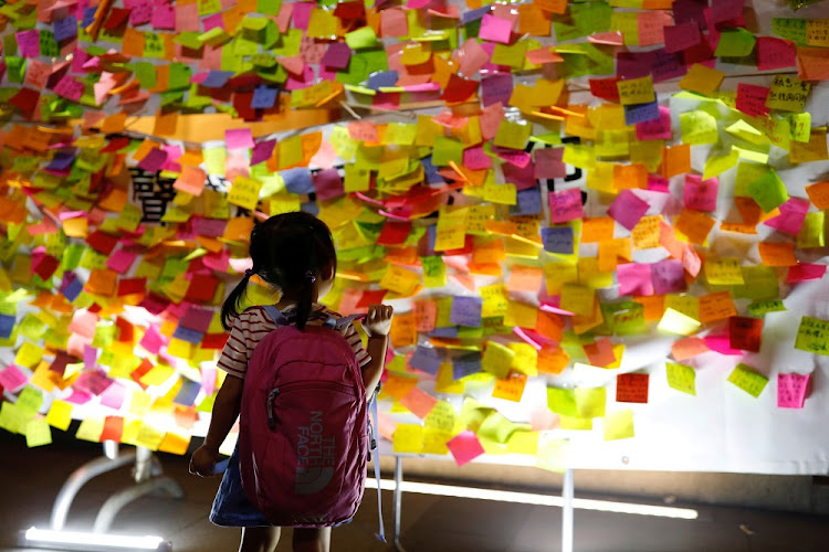 A child looks at messages in support of student leaders Joshua Wong, Nathan Law and Alex Chow, who were imprisoned for the 2014 pro-democracy Umbrella Movement protests, in Hong Kong, China, on Sunday. Picture: REUTERS