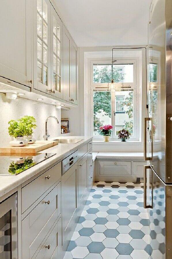 Cozinha com armários brancos, piso hexagonal azul e branco e janela branca com vasos de planta.