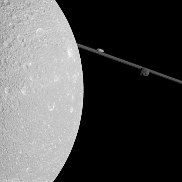 Photo: A Close Pass of Saturn's Moon Dione Image Credit: Cassini Imaging Team, ISS, JPL, +European Space Agency, ESA, +NASA http://apod.nasa.gov/apod/ap120521.html  What's that past Dione? When making its closest pass yet of Saturn's moon Dione late last year, the robotic Cassini spacecraft snapped this far-ranging picture featuring Dione, Saturn's rings, and the two small moons Epimetheus and Prometheus. The above image captures part of the heavily cratered snow-white surface of the 1,100 kilometer wide Dione, the thinness of Saturn's rings, and the comparative darkness of the smaller moon Epimetheus. The image was taken when Cassini was only about 100,000 kilometers from the large icy moon. Future events in Cassini's continuing exploration of Saturn and its moons include tomorrow's flyby of Titan and imaging the distant Earth passing behind Saturn in June.