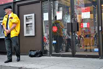 Photo: A security guard stands in front of the bank to ensure no further damage is done to the property, but the 'Black Bloc' is long gone by now.
