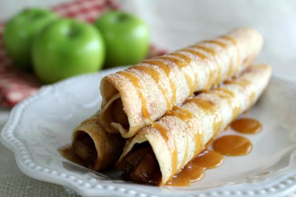 Caramel Apple Taquitos On A Plate With Caramel Drizzled On Top.