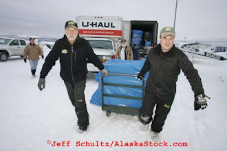 Photo: Saturday February 17th 2007 At Merrill field in Anchorage, Volunteer bush pilots Bill Mayer and Greg Niesen move bales of straw to thier plane to fly them  out to some of the first checkpoint along the Iditarod Trail in preparation for the 2007 Iditarod sled dog race.