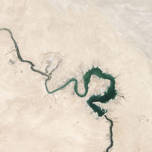 Aerial view of a snaking green river through a tan desert