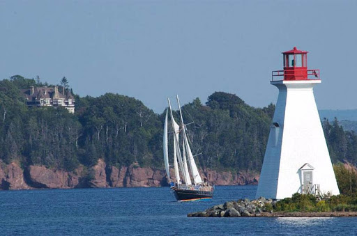 A sailing vessel passes a lighthouse in Baddeck, Nova Scotia.