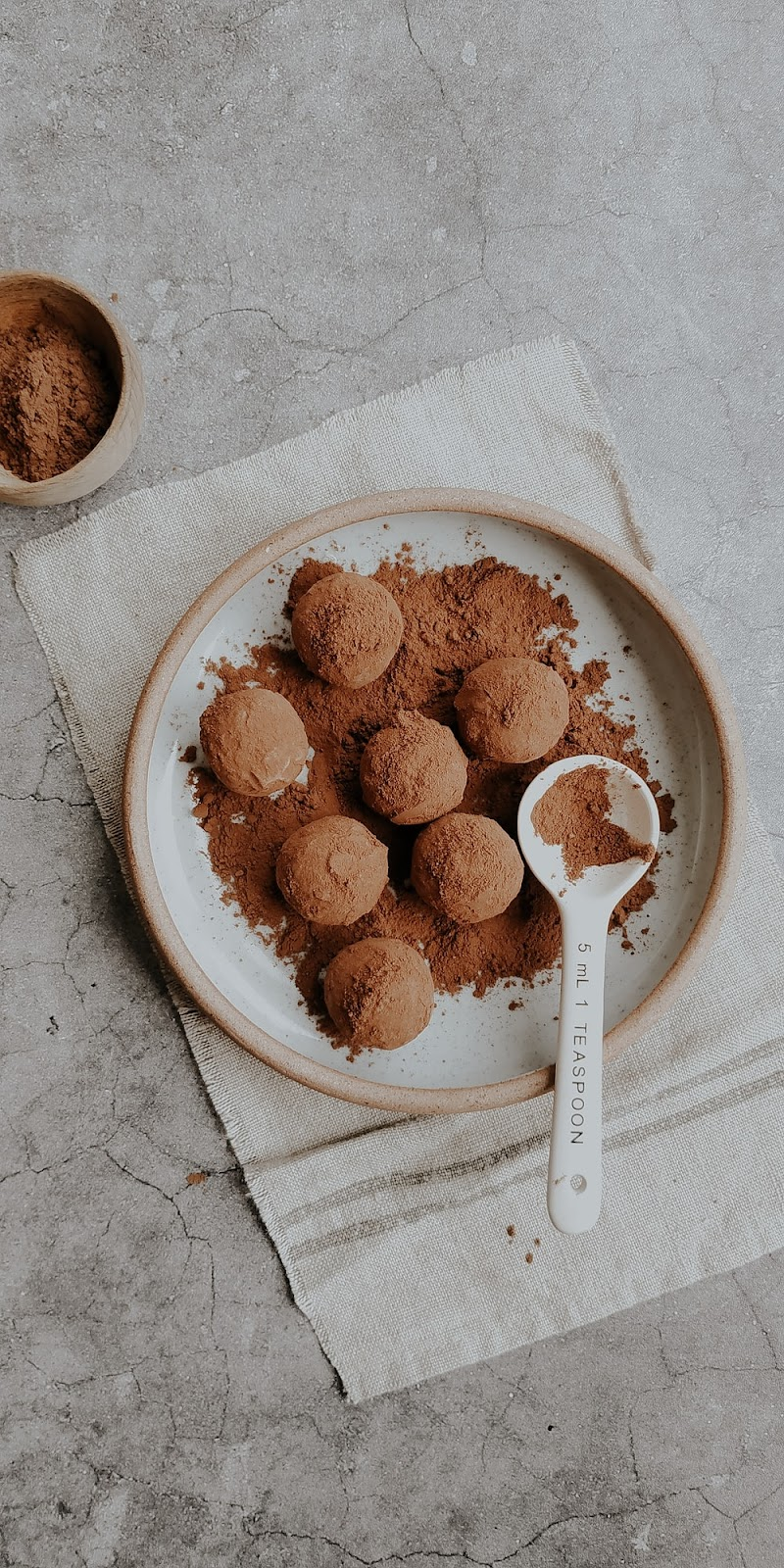 chocolate truffles with organic cocoa powder on a white ceramic bowl