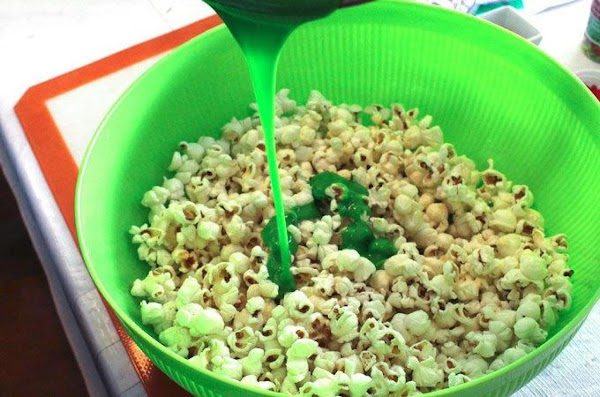 Slowly pour the marshmallow mixture over the popcorn. Using a wooden spoon, gently fold...