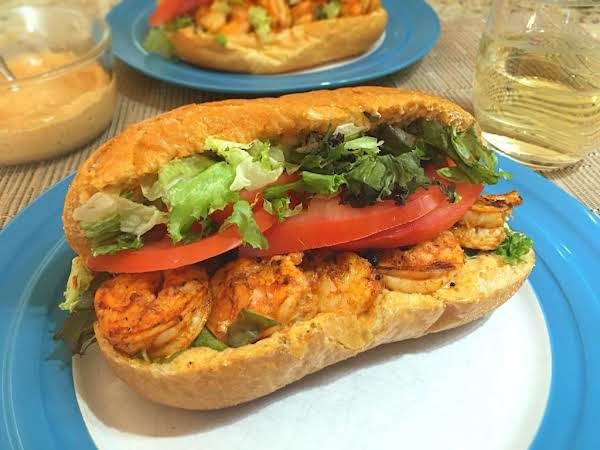 A Few Grilled Shrimp In A Hoagie Topped With Tomato Slices And Lettuce.