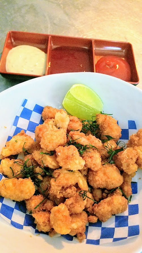 Shipwreck PDX food dish of Tom Yum Popcorn Shrimp with fried kaffir lime leaves, cocktail sauce, Lingham's Original hot sauce, tartar sauce