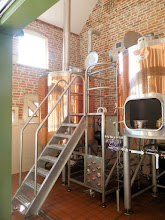 Photo: Mash tun (right) and copper (left with vent pipe). By means of the manifold beneath the steps the wort can be delivered from the mash tun to the copper to be boiled, and thence through the heat exchanger to a fermenting vessel in the next room.