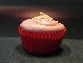 Photo: Vanilla cupcake topped with pink vanilla cream cheese icing and sprinkles