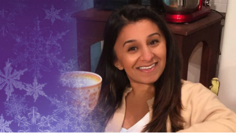 Shani holding a cup with christmas snowflakes around the left edge of the image