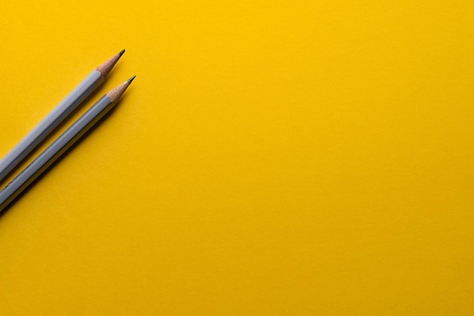 Dwa ołówki na żółtej kartce papieru. Stworzenie kalendarza publikacji jest nieodzowną częścią dobrej strategii zarządzania treścią dla blogerów.