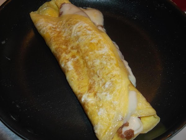 Using an egg turner or spatula, fold omelette in half or into thirds; remove...