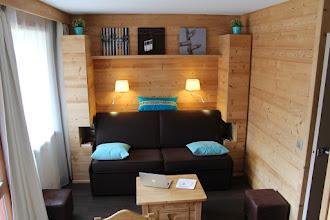 """Photo: Coin salon, canapé-lit """"bed express"""", placards sur mesure, table basse-coffre, 2 poufs."""