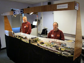 "Photo: 003a Having spent all these years ""getting aroundtuit"" regarding having a photo session away from exhibition hustle and bustle, I completely failed to get an overall photo showing the complete layout, so in order for you to see it in its fullness, I have resorted to using this photo that I took at Narrow Gauge South 2012 showing Tim (right) with fellow Sussex Downs 009 Group member Mark Holland and the layout in essentially its current state ."