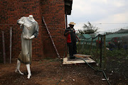 A shop mannequin stands guard over a vegetable garden at Takalani Home for the Mentally Handicapped on February 2, 2017 in Soweto, South Africa.