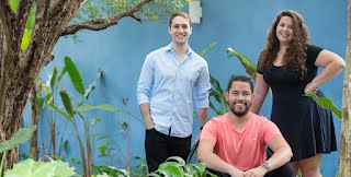 Cuidas founders João, Matheus, and Deborah pose together in front of a blue wall.