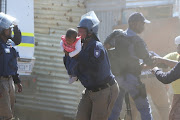 A Nelson Mandela Bay metro police officer takes the child to safety after her father threw her off the roof of a shack at the Joe Slovo informal settlement.