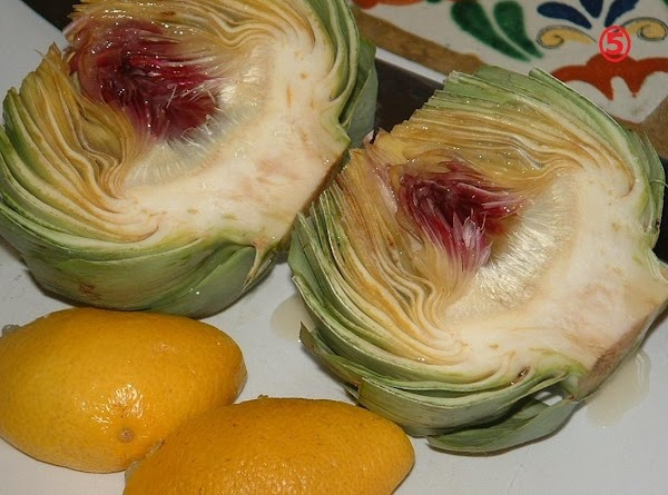 Using that really sharp knife again, slice the artichoke in half along its axis....