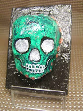 Photo: The Green Sugar Skull. (sold) 2.5 x 3.5 x 1.5 inches. Acrylics, metallic ink, and glitter on papier-mâché made from recycled store receipts. Sealed with a glossy varnish. Title and signature on the back. ©Marisol McKee.