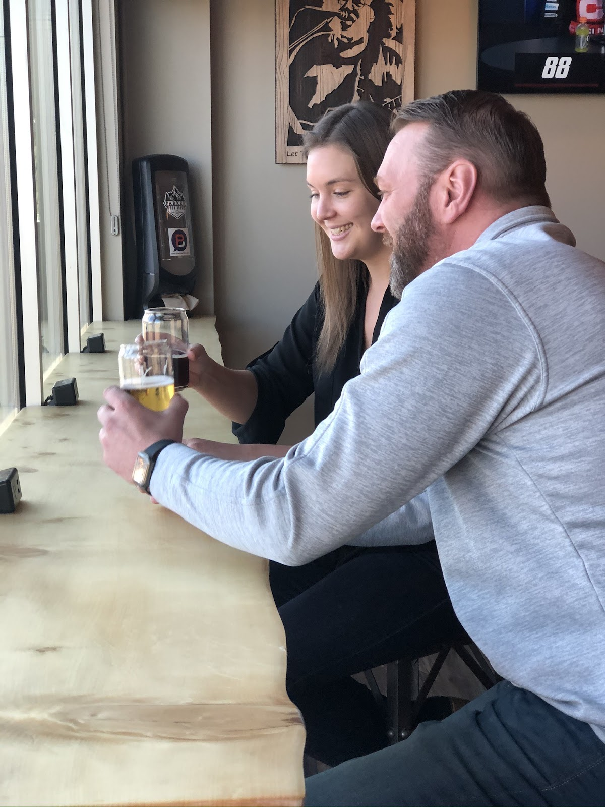 two people holding beers