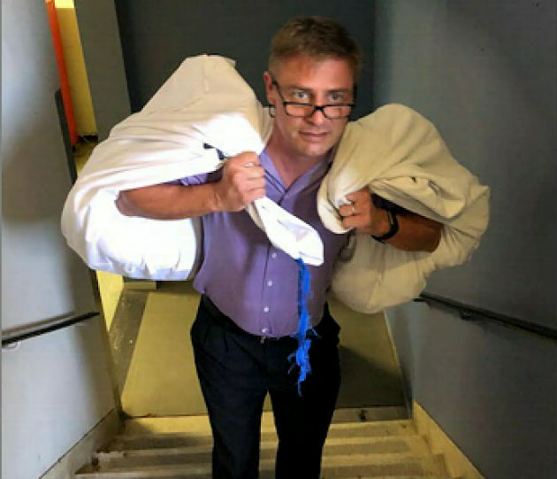 Provincial Hospital haematology department head Dr Neil Littleton takes clean linen up the stairs to his unit