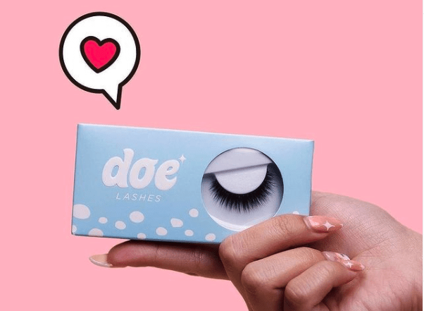 Image of a person's hand holding a package of Doe Lashes with a heart emoji above it