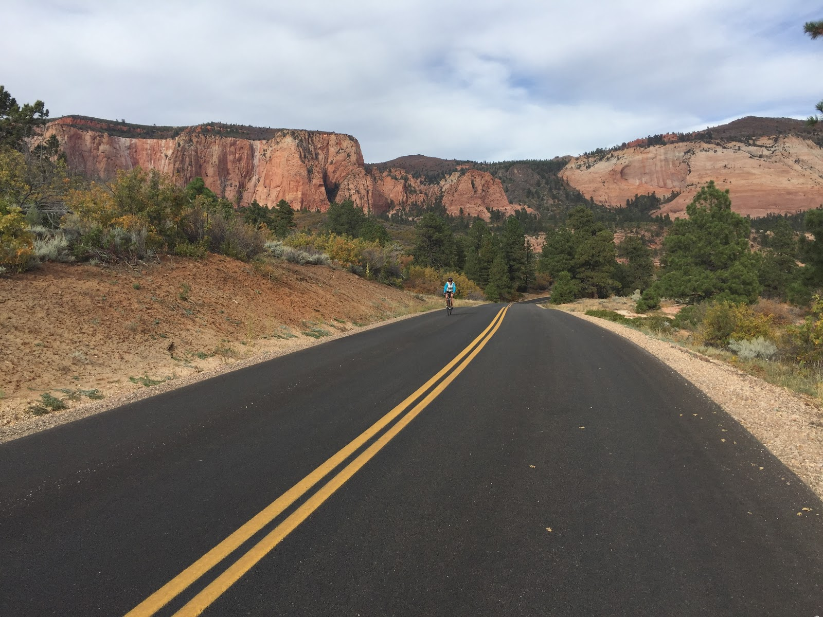 Bicycling Kolob Terrace - cyclist on road with mountains behind