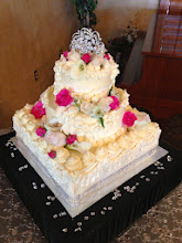 Photo: Ornate wedding cake (after glance) all in Ivory whipped cream frosting. This work of art features mini & large rosettes studded w/edible pearls, ribbon border around bottom, swoop ribbon border on middle tier, mini frosting roses w/foliage. Silver diamond wrap around bottom. Fresh  Ivory & Hot Pink roses w/fresh foliage.