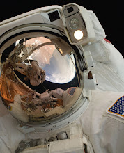 Photo: A close-up of Astronaut John Grunsfeld shows the reflection of Astronaut Andrew Feustel, perched on the robotic arm and taking the photo. The pair teamed together on three of the five spacewalks during Servicing Mission 4 in May 2009.The Hubble Space Telescope is a project of international cooperation between NASA and the European Space Agency. NASA's Goddard Space Flight Center manages the telescope. The Space Telescope Science Institute conducts Hubble science operations.Goddard is responsible for HST project management, including mission and science operations, servicing missions, and all associated development activities.