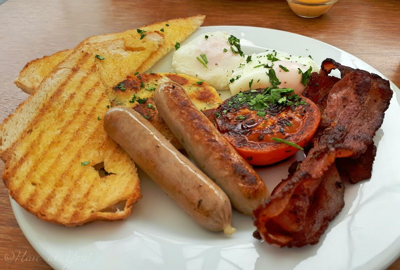 plate filled with sausages, bacon, poached eggs, tomato and toasts