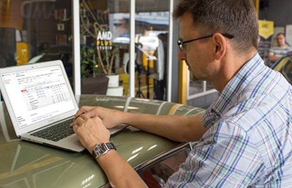 man looking at graphs on a laptop