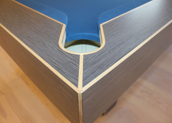 the corner pocket of the arc table in a home with black painted wooden edges