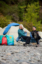 Photo: Two women laughing and relaxing while on a white water rafting trip along the wild and scenic Rogue River in southern Oregon.