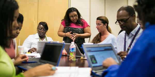 Teachers on Chromebooks during a meeting