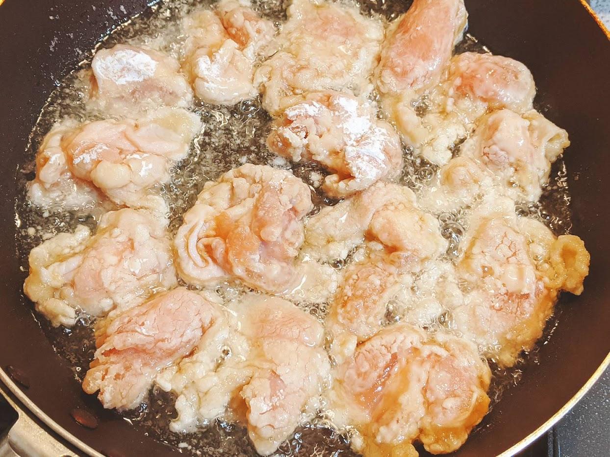 衣をつけた鶏肉をフライパンで少なめの油で揚げている画像